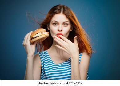red-haired woman with red lips eating a burger and licks his fingers