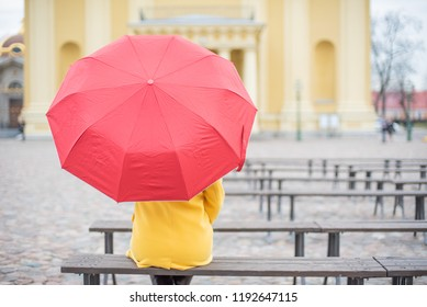 Red-haired woman is sitting with her back in a yellow coat with a red umbrella. A young girl sits on a bench alone at the cathedral.