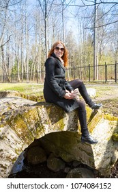 Red-haired woman sitting on a bridge in a Oranienbaum park