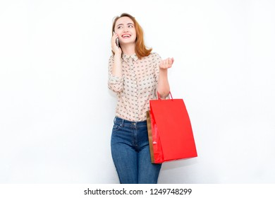Red-haired woman stands on a light background in stylish casual clothes with bags after shopping and talking on the phone. Modern concept of fashion, shopping, discounts, sales.