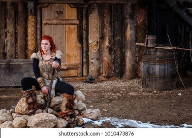 Red-haired woman is a Viking. Against the backdrop of a village or an ancient settlement. In the hands of a sword