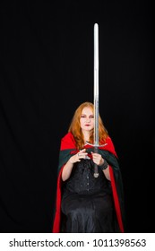 red-haired woman wearing in a long black gown and green robe juggles two-handed sword