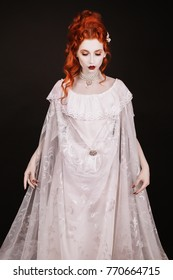 Red-haired woman in white dress with pale skin on a black background. Woman vampire in the gothic style in the Halloween look