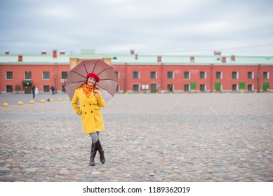 A red-haired woman in a yellow coat and a red beret is jumping with a red umbrella. A smiling beautiful woman in striped pants and a warm jacket flies with an umbrella, like Merry Poppins.