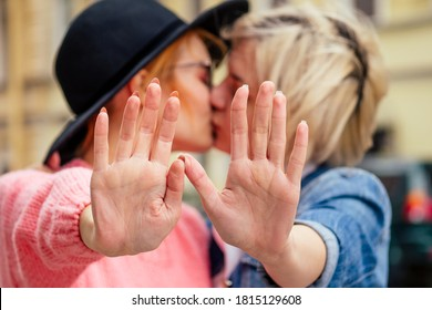 redhaired young ginger woman feeling love to her blonde girlfriend in Europe streets shoving stop hands gesture