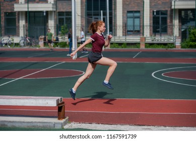 Red-haired young girl runs in the stadium. Student delivers standards for running outdoors. Young woman running on the football field