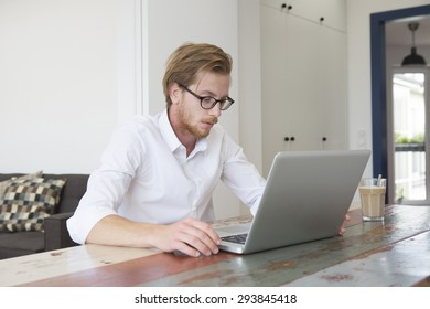 red-haired young man sitting at table and looking at his laptop