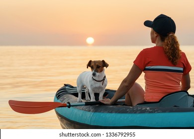Red-haired young woman is rowing on an inflatable kayak by the sea with a dog Jack Russell Terrier on a background of pink sunrise in beautiful nature. Great disk of the rising sun. Sun rays. Sport