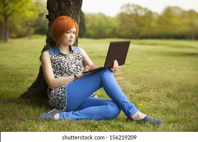red-haired young woman sitting in park with laptop