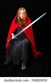 red-haired young woman wearing in a black long dress and red robe with tippet sits with knightly sword in her hands, on dark background
