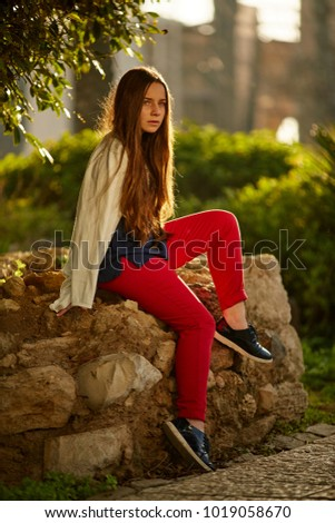 eb4b7ddc6acf4 redhead 12 years old girl sitting on a rock and busy thinking, wearing  white shirt, red pants and black shose - Image