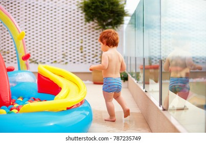 redhead baby boy having fun running around inflatable kid pool at the patio