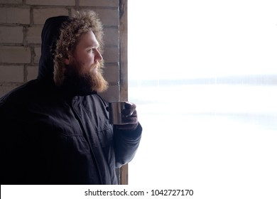 Redhead bearded man in polar jacket in hood holding cup of hot coffee or tea and looking out the window