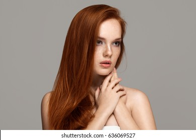 Redhead beautiful girl with long straight hair. Attractive beauty woman with freckles on her face. Closeup portrait, isolated on grey background. Hands near the face