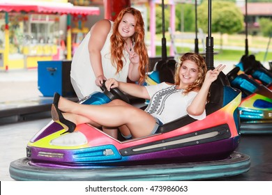 Redhead and Blonde women with large sizes have fun in the dodgems and show the peace sign