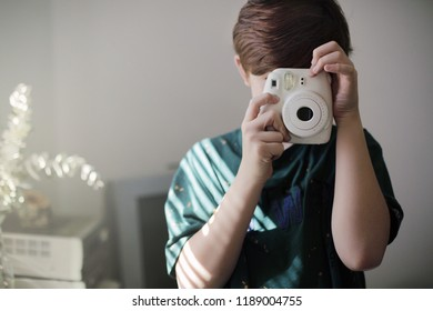 Redhead boy with instant print camera