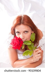 redhead bride - young attractive woman in bridal dress, with red rose held close to her face