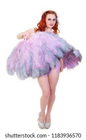 Redhead burlesque dancer in silver high heels with pink feather fans