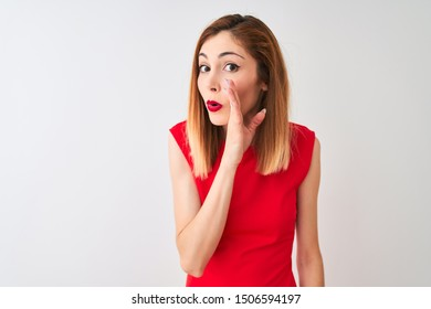 Redhead businesswoman wearing elegant red dress standing over isolated white background hand on mouth telling secret rumor, whispering malicious talk conversation