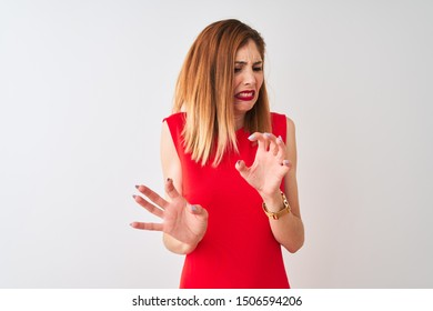 Redhead businesswoman wearing elegant red dress standing over isolated white background disgusted expression, displeased and fearful doing disgust face because aversion reaction. With hands raised.