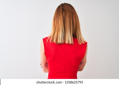 Redhead businesswoman wearing elegant red dress standing over isolated white background standing backwards looking away with crossed arms