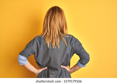 Redhead caucasian business woman over yellow isolated background standing backwards looking away with arms on body