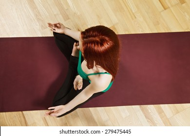 Redhead caucasian woman meditating in lotus position high angle view