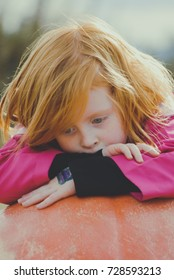 Redhead child contemplating life on top of a giant pumpkin
