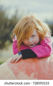 Redhead child with happy grin, resting on a giant pumpkin