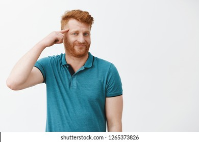 Redhead displeased guy discussing weird friend who got insane recently, making stupid decisions. Portrait of mature european man rolling finger on temple and mocking someone who make fool of himself