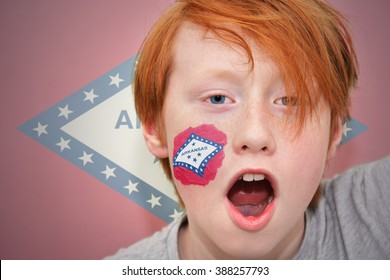 redhead fan boy with arkansas state flag painted on his face.