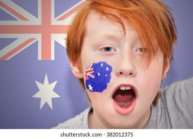 redhead fan boy with australian flag painted on his face.