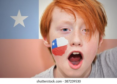redhead fan boy with chilean flag painted on his face.