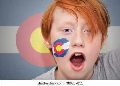 redhead fan boy with colorado state flag painted on his face.