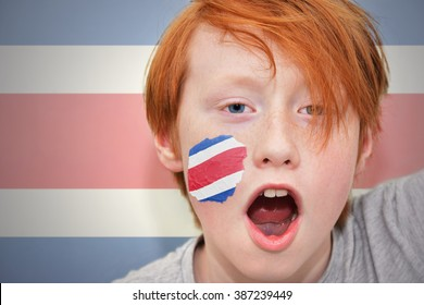 redhead fan boy with costa rican flag painted on his face.