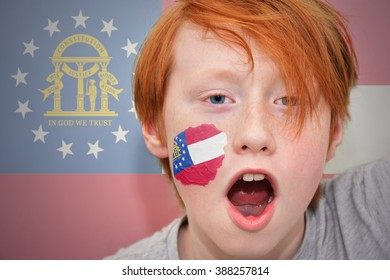 redhead fan boy with georgia state flag painted on his face.