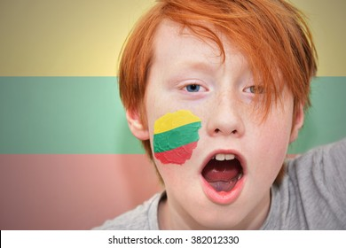redhead fan boy with lithuanian flag painted on his face.
