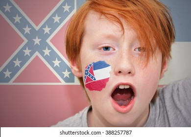 redhead fan boy with mississippi state flag painted on his face.