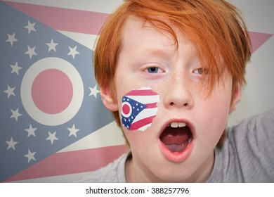 redhead fan boy with ohio state flag painted on his face.