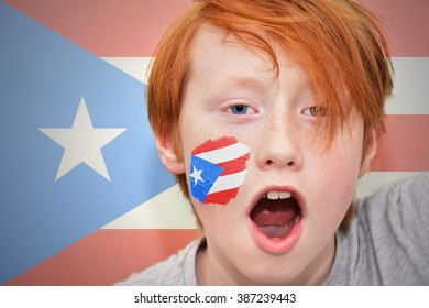 redhead fan boy with puerto rican flag painted on his face.