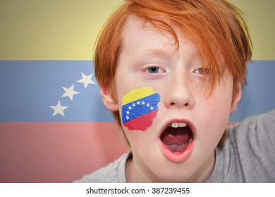 redhead fan boy with venezuelan flag painted on his face.