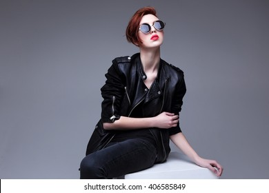 Redhead fashion model in sunglasses and black leather jacket. Pixie cut hairstyle. Punk, rock style fashion