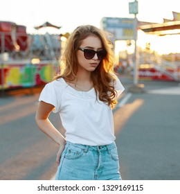 Redhead fashionable young hipster woman in a white T-shirt in stylish sunglasses in blue vintage jeans is resting in an amusement park on a sunset background. Attractive girl on vacation.