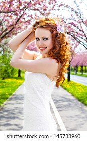 Redhead girl at blooming tree's alley, springtime