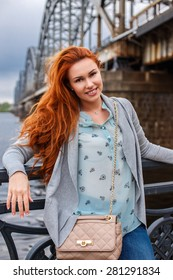 Redhead girl in casual clothes posing on paraphet near the river