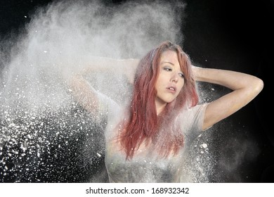 Redhead girl with colored powder exploding around her and into the background.