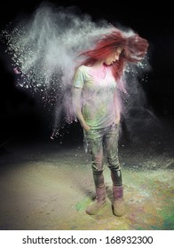 Redhead girl with colored powder trailing behind her hair that she is flinging up.