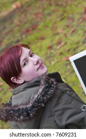Redhead girl with computer in an autumn park looking up-back over the shoulder.