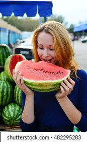 Redhead girl eating a watermelon