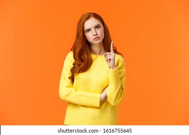 Redhead girl express disapproval as shaking her finger at someone with disappointed angry face, frowning give warning, prohibit unacceptable behaviour, standing displeased orange background